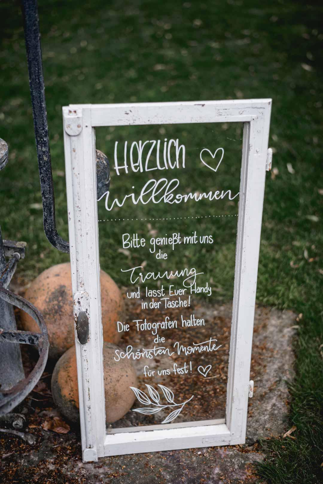 Willkommensschild bei der Hochzeit mit einem alten Fenster