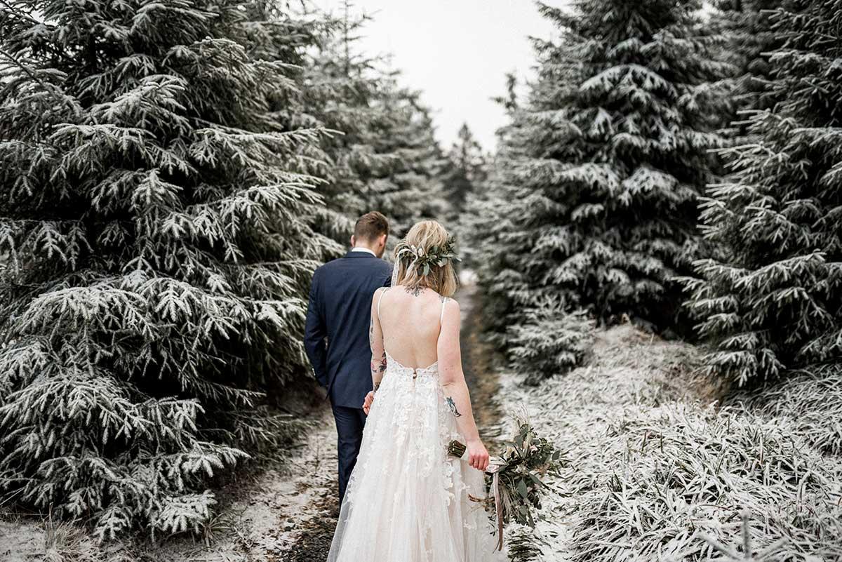 Brautpaar läuft zwischen Tannen hindurch