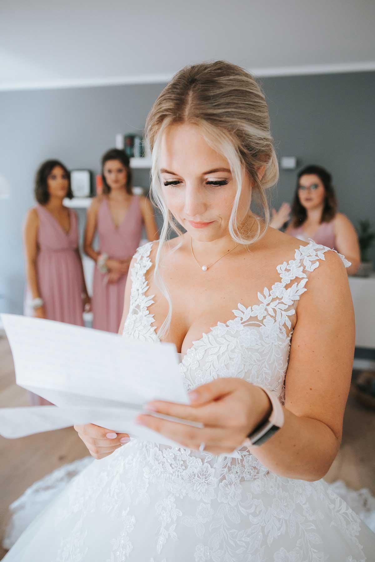 Braut liest beim Getting Ready noch einmal ihr Eheversprechen