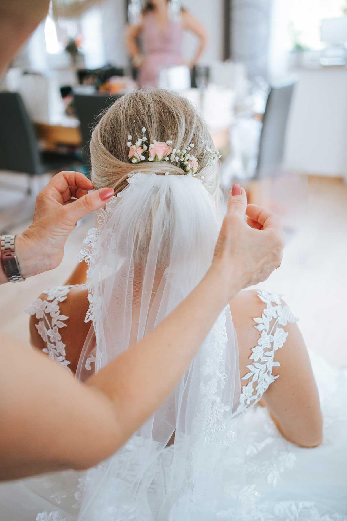 Braut beim Getting Ready mit Schleier und Blumen im Haar