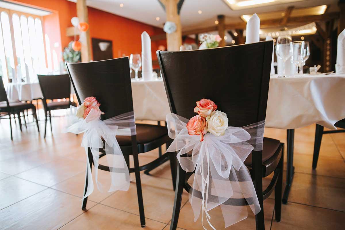 Dekoration der Stühle mit Stuhlschleifen und Blumen