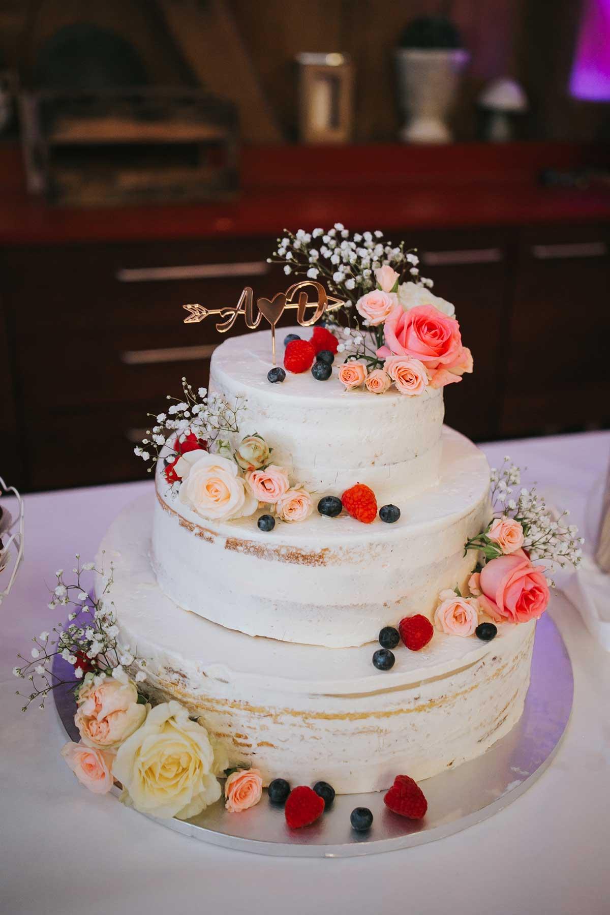 Hochzeitstorte im seminaked Look mit Blüten und Beeren