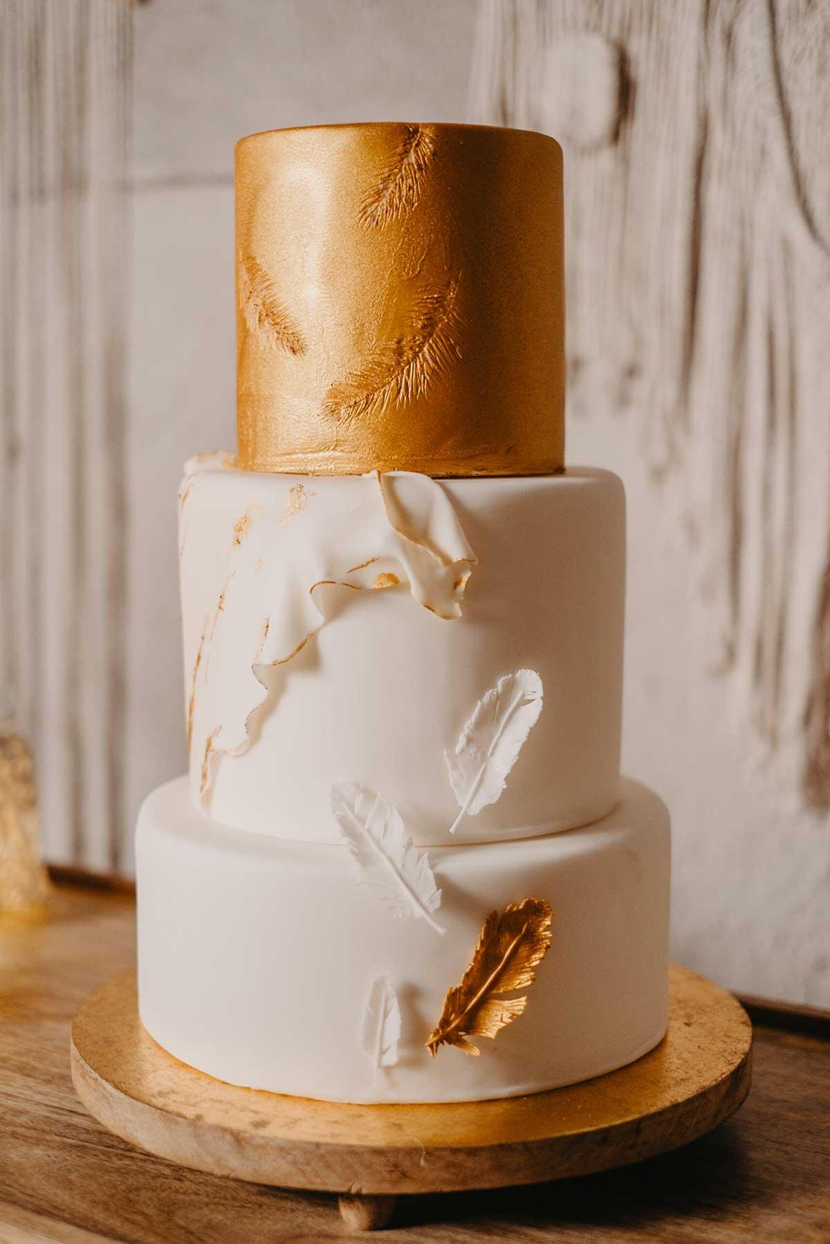 Hochzeitstorte in Gold und Weiß mit Federn