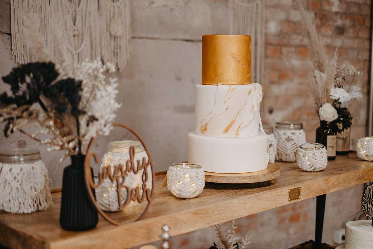 Hochzeitstorte in Gold und Weiß mit Federn bei der Candybar