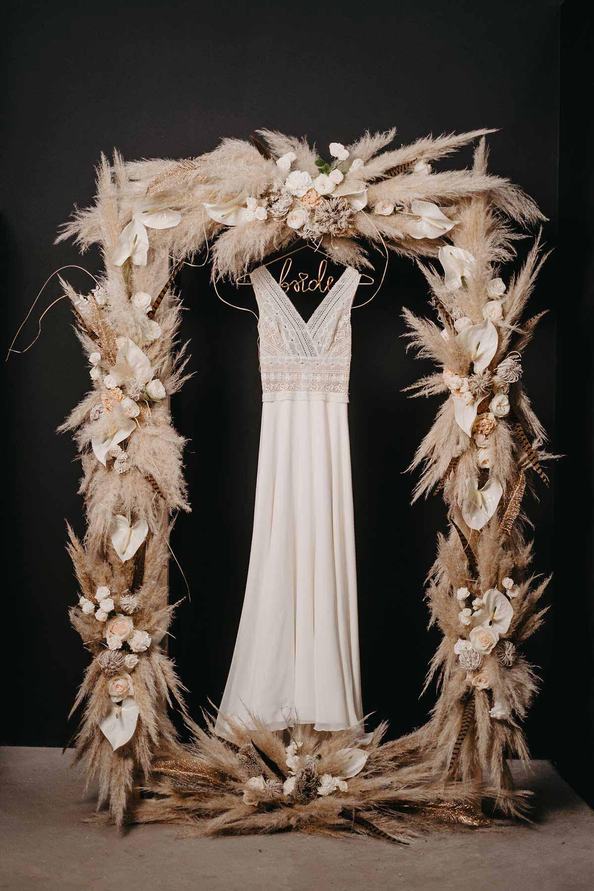 Brautkleid mit Bride Kleiderbügel im Rahmen aus Trockenblumen