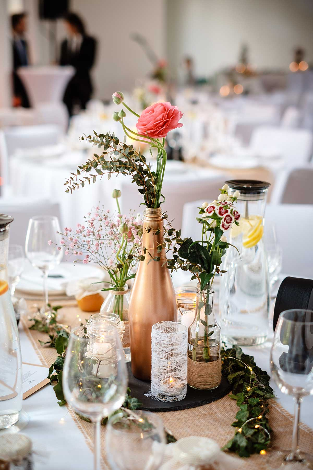 Tischdeko im Vintagestil mit einer Mischung aus eleganten Vasen