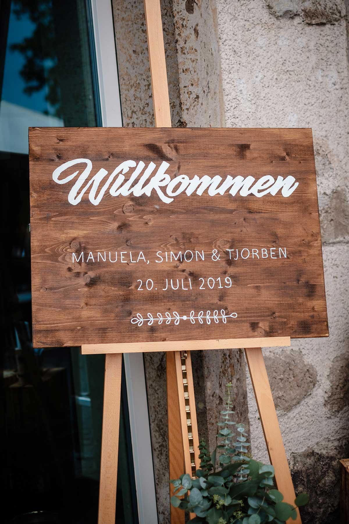 Willkommensschild aus Holz auf einer Staffelei