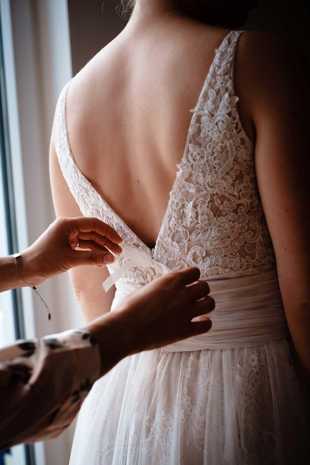 Braut beim verschließen von ihrem Brautkleid