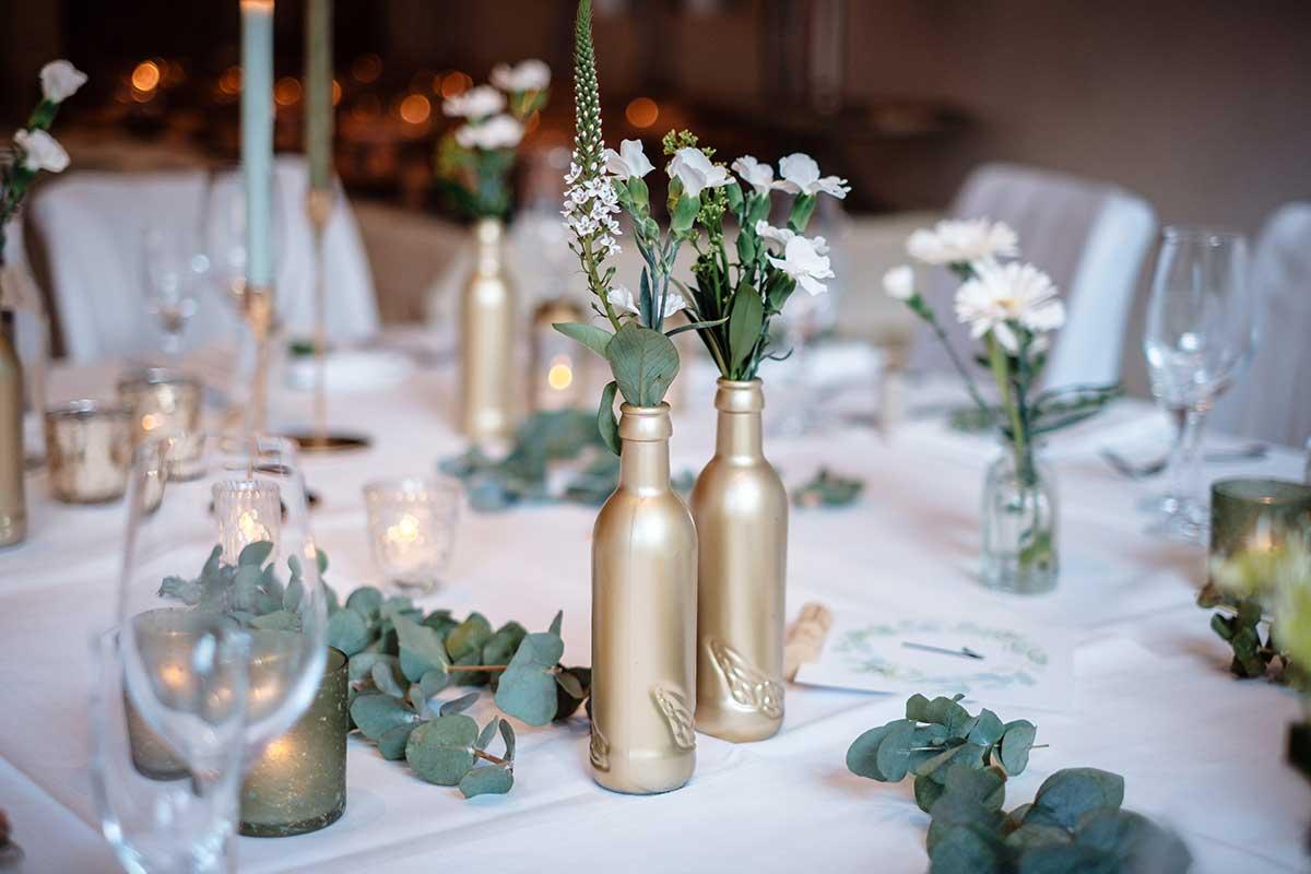 In Gold besprühte Flaschen für die Tischdeko