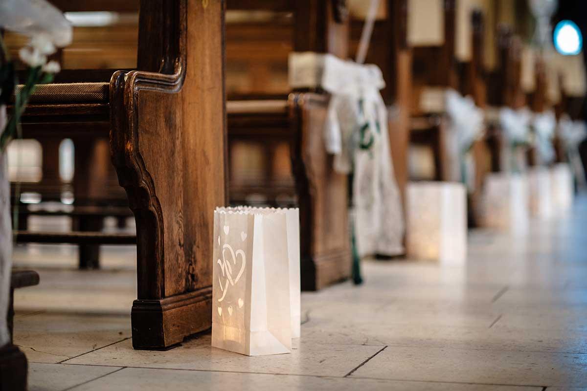 Dekoration der Sitzbänke in der Kirche mit kleinen Tüten und Kerzen