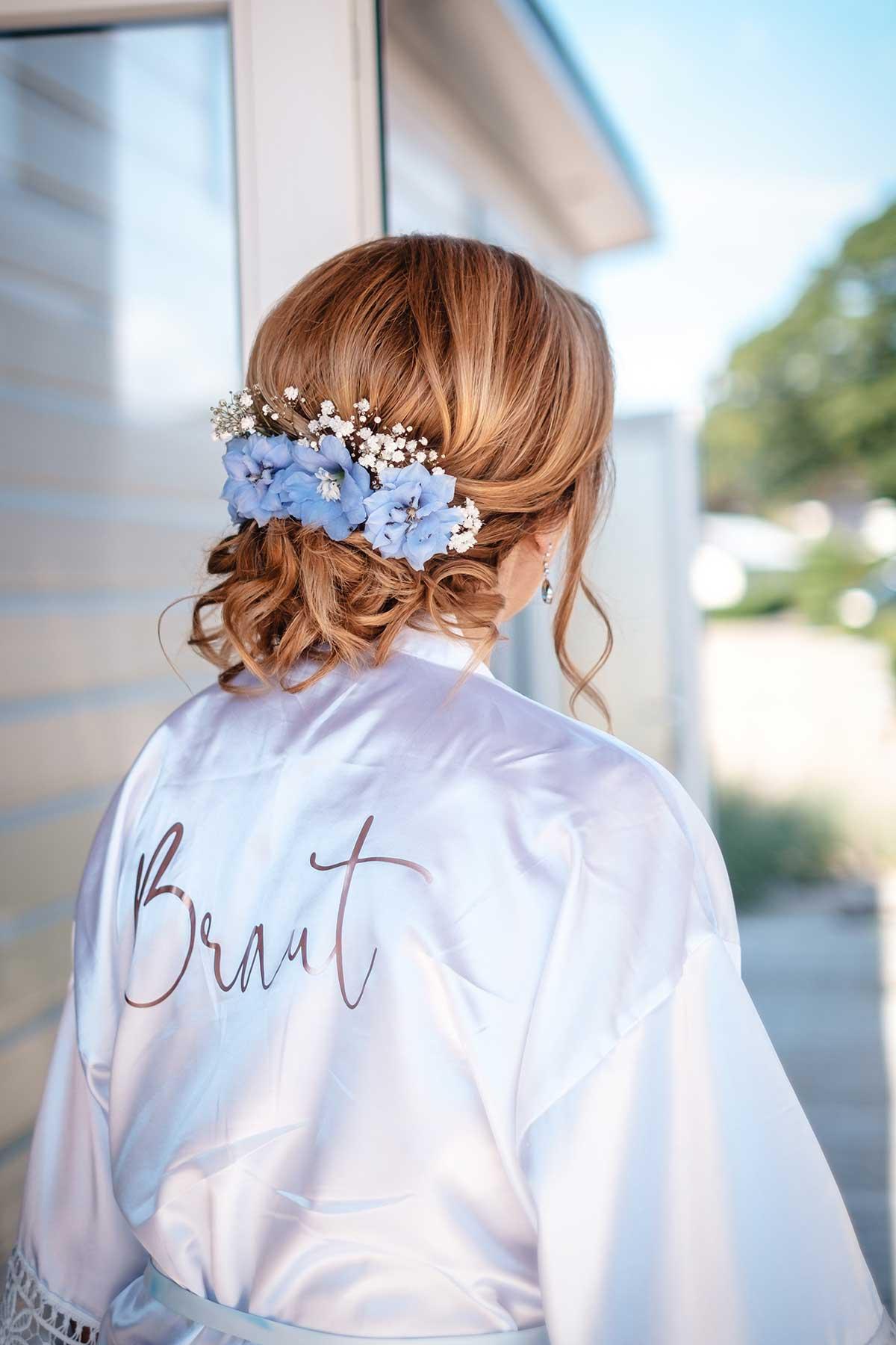 Braut im Morgenmantel mit Blumen im Haar