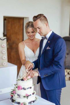Braut und Bräutigam schneiden die Hochzeitstorte an