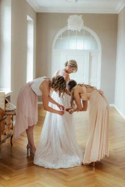Brautjungfern und Trauzeugin helfen der Braut beim Getting Ready