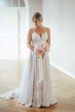 Braut mit ihrem Brautstrauß aus weißen und rosa Rosen und Pfingstrosen
