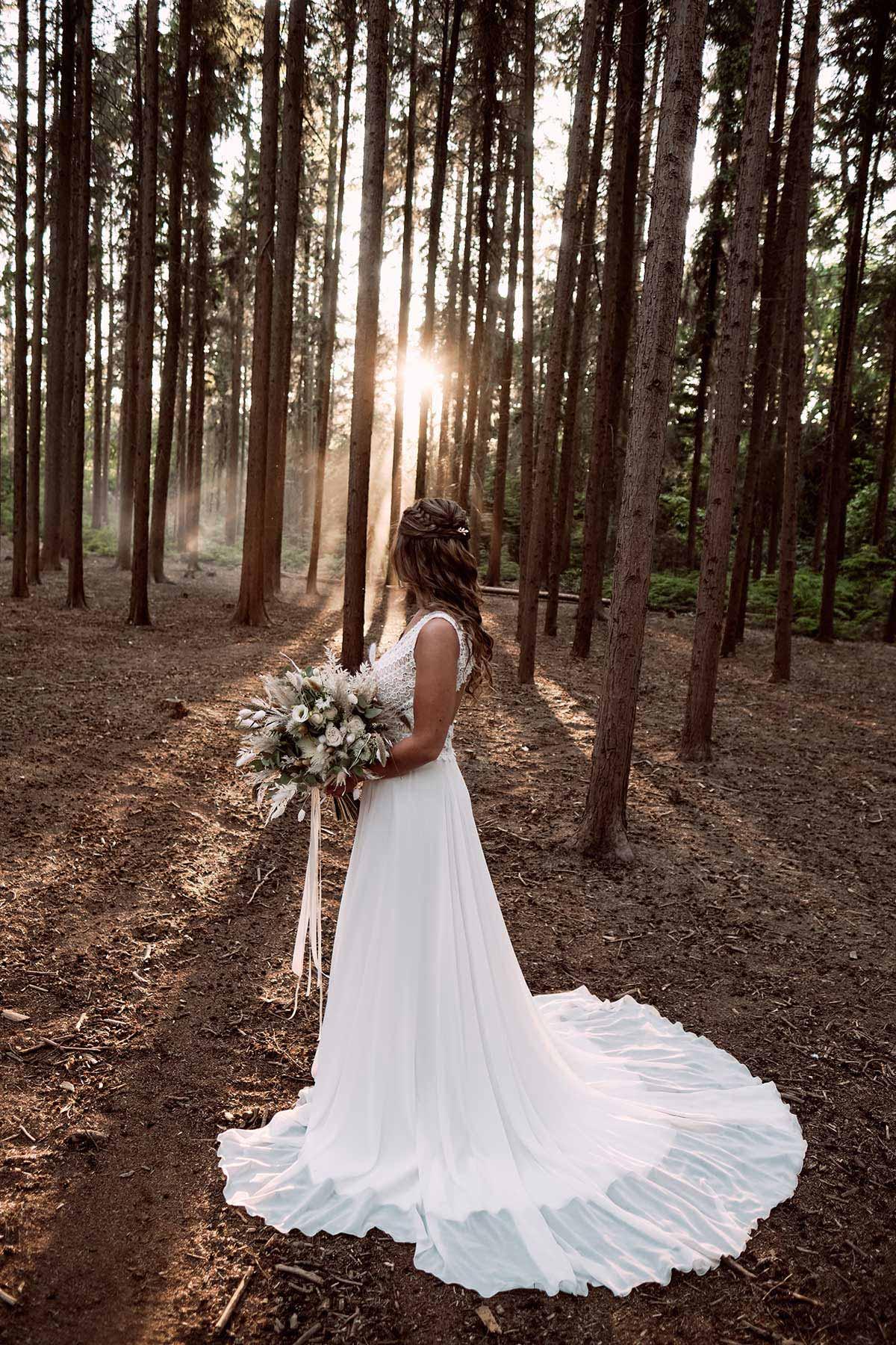 Braut im Brautkleid und Brautstrauß im Wald