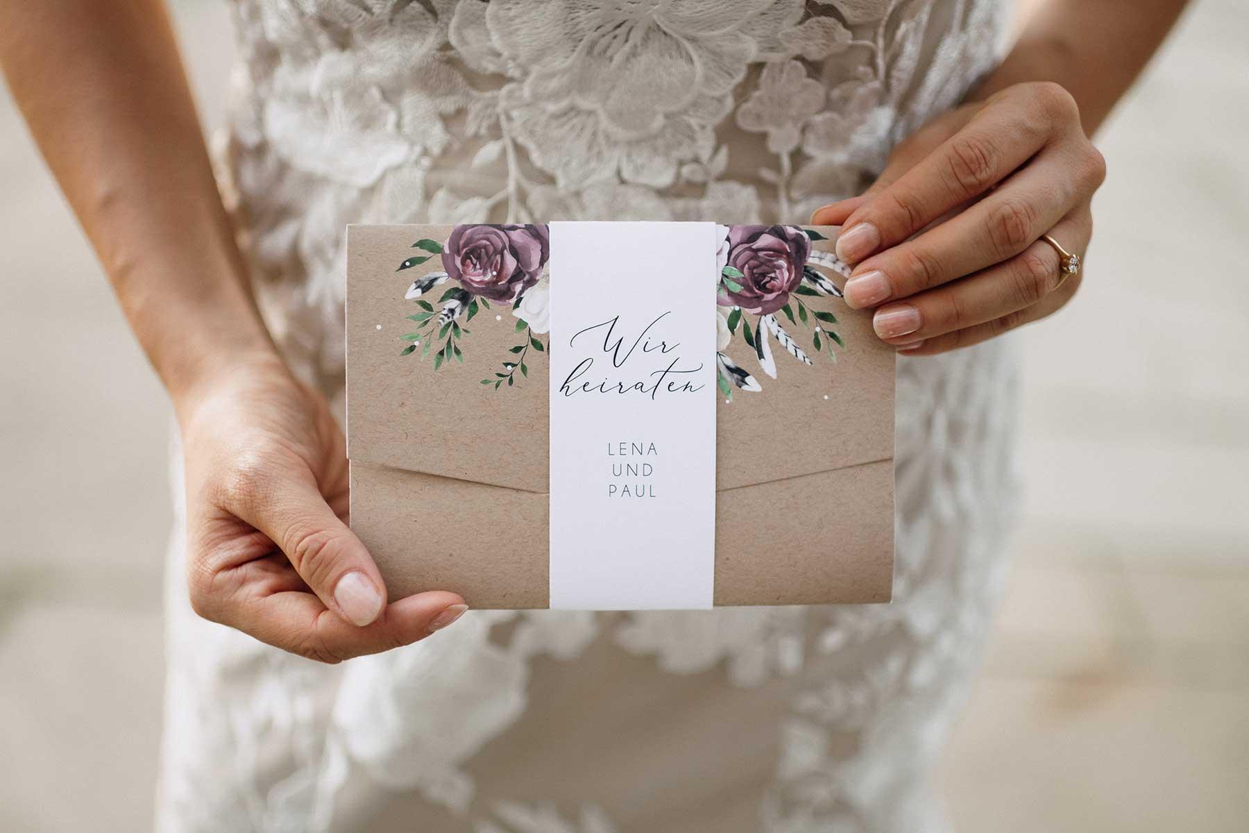 Braut hält Pocketfold Einladung zur Hochzeit in der Hand