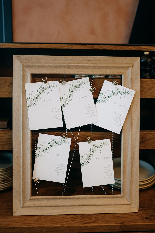 Einzelne Karten für den Sitzplan bei der Hochzeit an einem Bilderrahmen