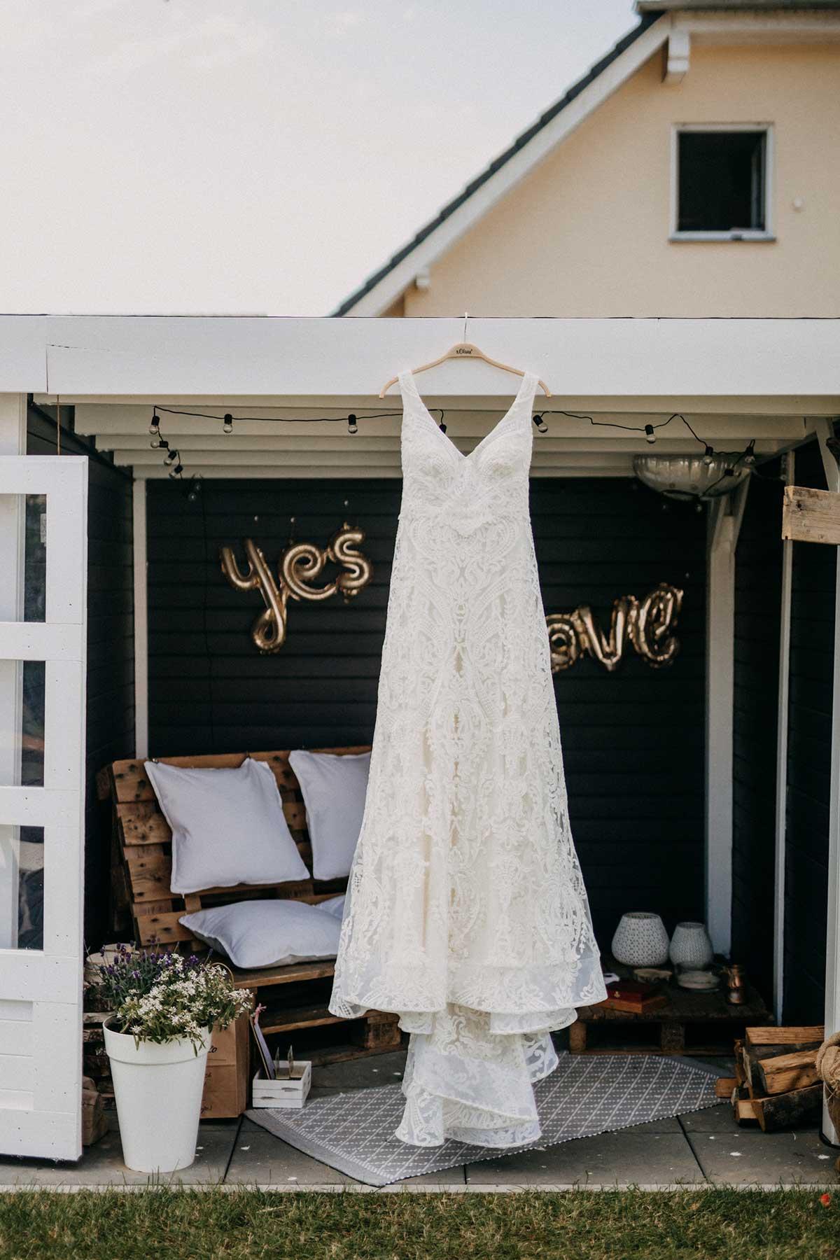Brautkleid hängt im Garten