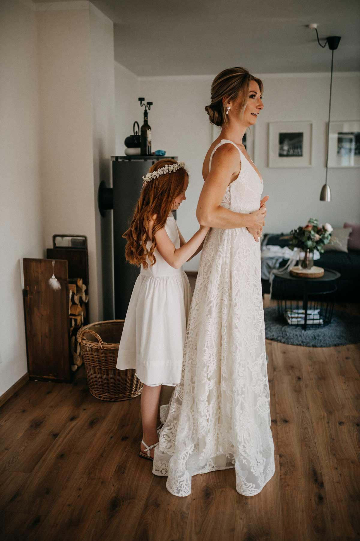 Tochter hilft der Mutter beim Anziehen des Brautkleids