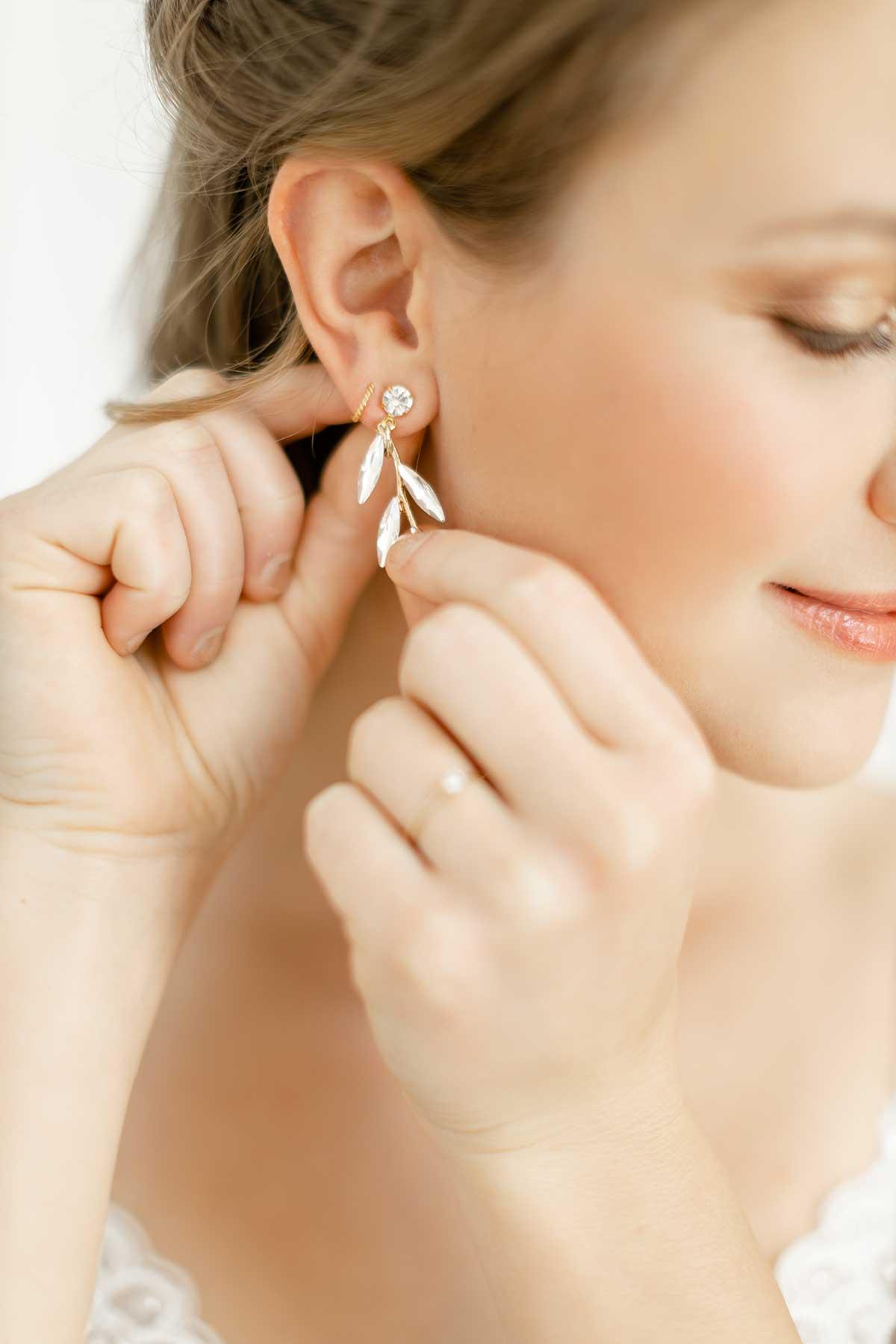 Braut steckt sich ihren Ohrring an