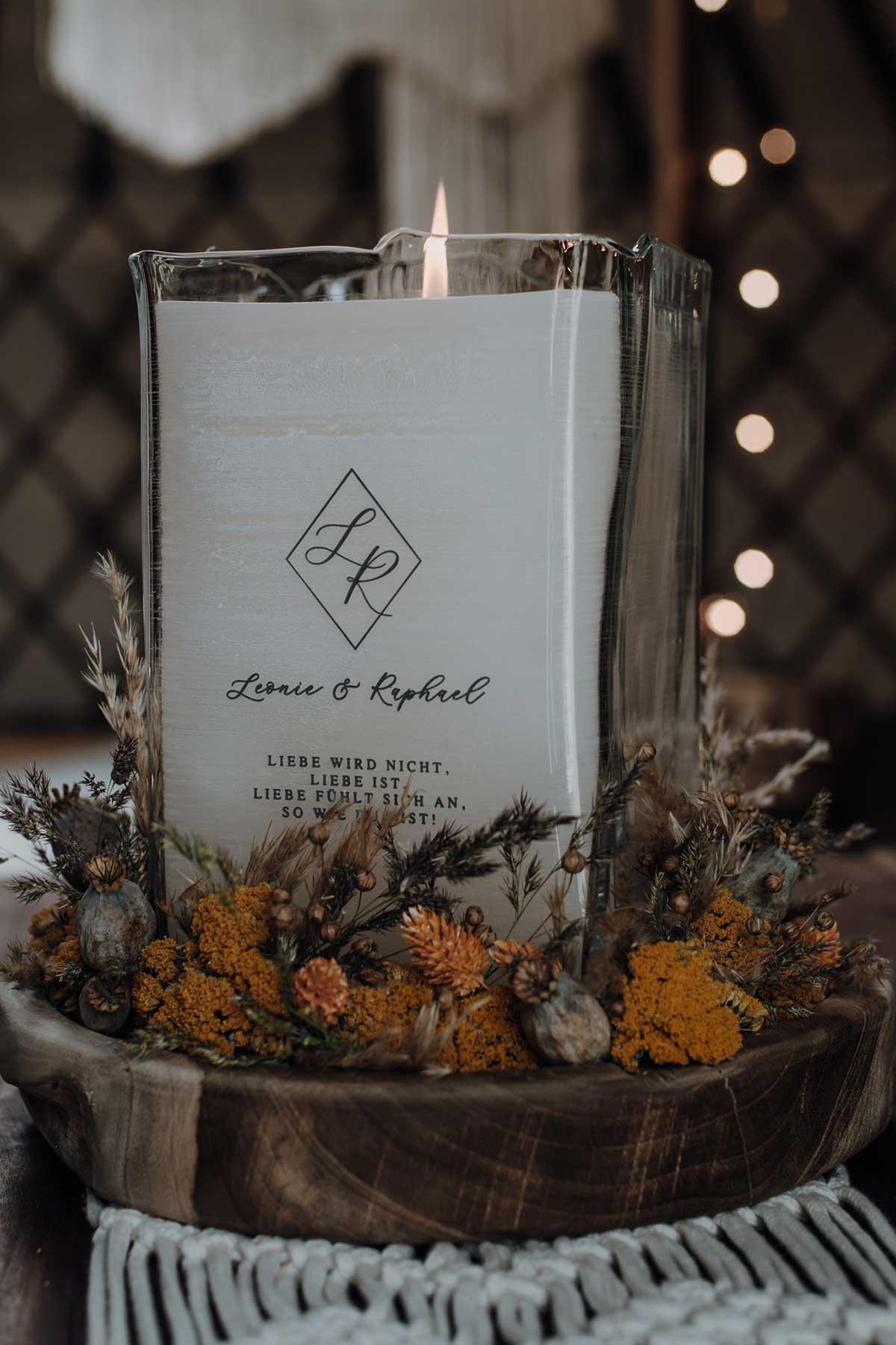 Kerze in einem Glas mit Initialen von Braut und Bräutigam