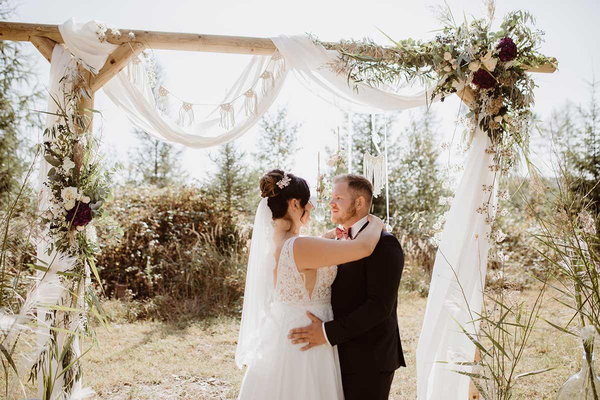 Braut und Bräutigam unter dem Traubogen