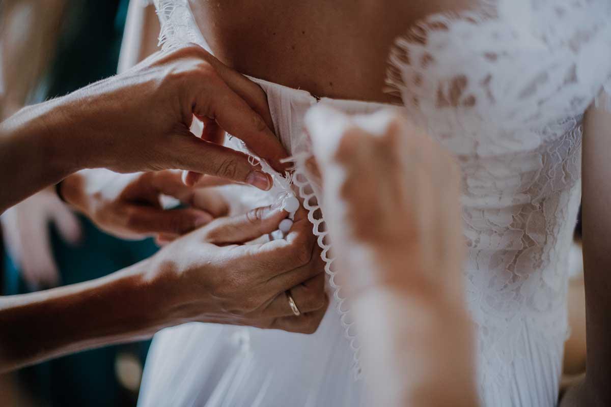Braut beim Getting Ready wo ihr Kleid zugeknöpft wird