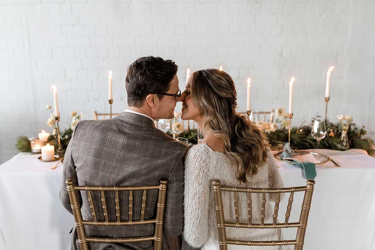 Braut und Bräutigam verliebt sitzend am Brautpaar-Tisch