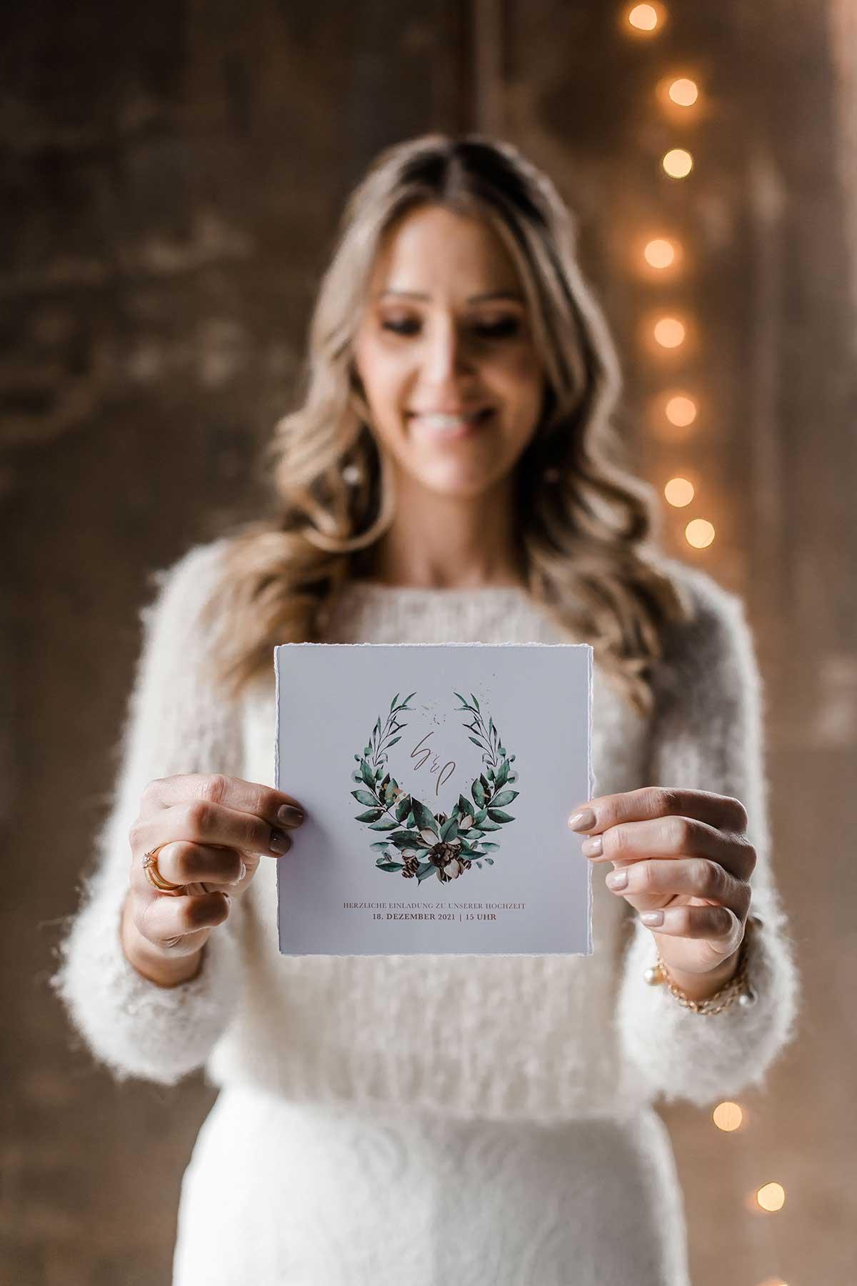 Braut hält Einladungskarte zur Hochzeit