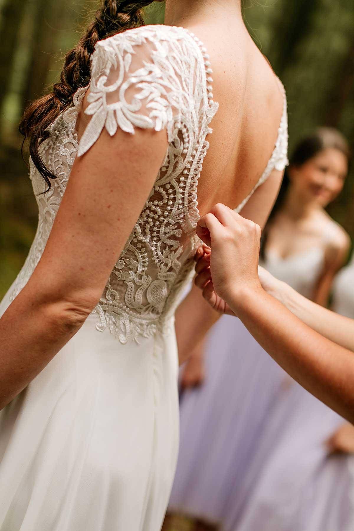 Trauzeugin knüpft der Braut das Brautkleid zu