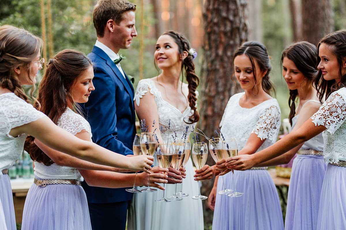Brautpaar stößt mit Gästen bei der Hochzeit an