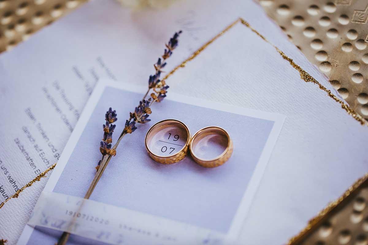Ringe liegen auf der Einladung zur Hochzeit