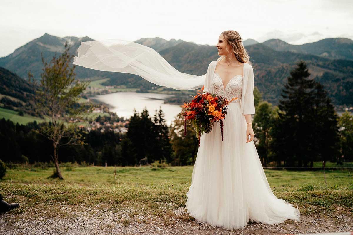 Braut mit Brautstrauß und fliegendem Schleier