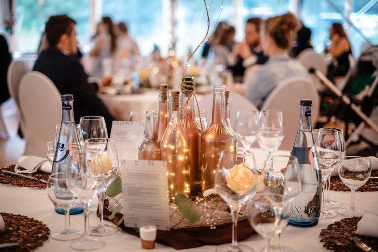 Tischdekoration mit besprühten Flaschen bei der Hochzeit