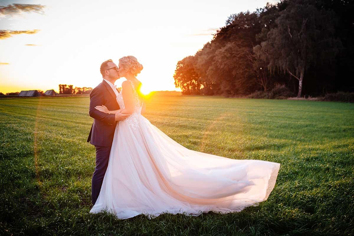 Braut und Bräutigam beim Foto-Shooting im Sonnenuntergang