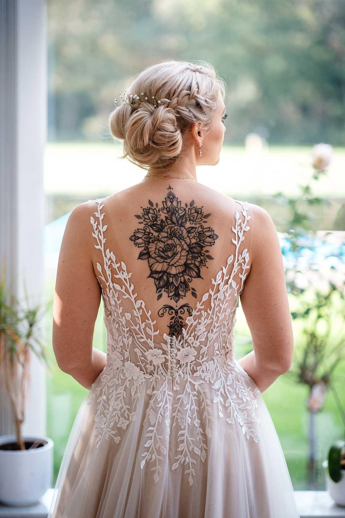 Braut im Brautkleid mit großem Rückentattoo