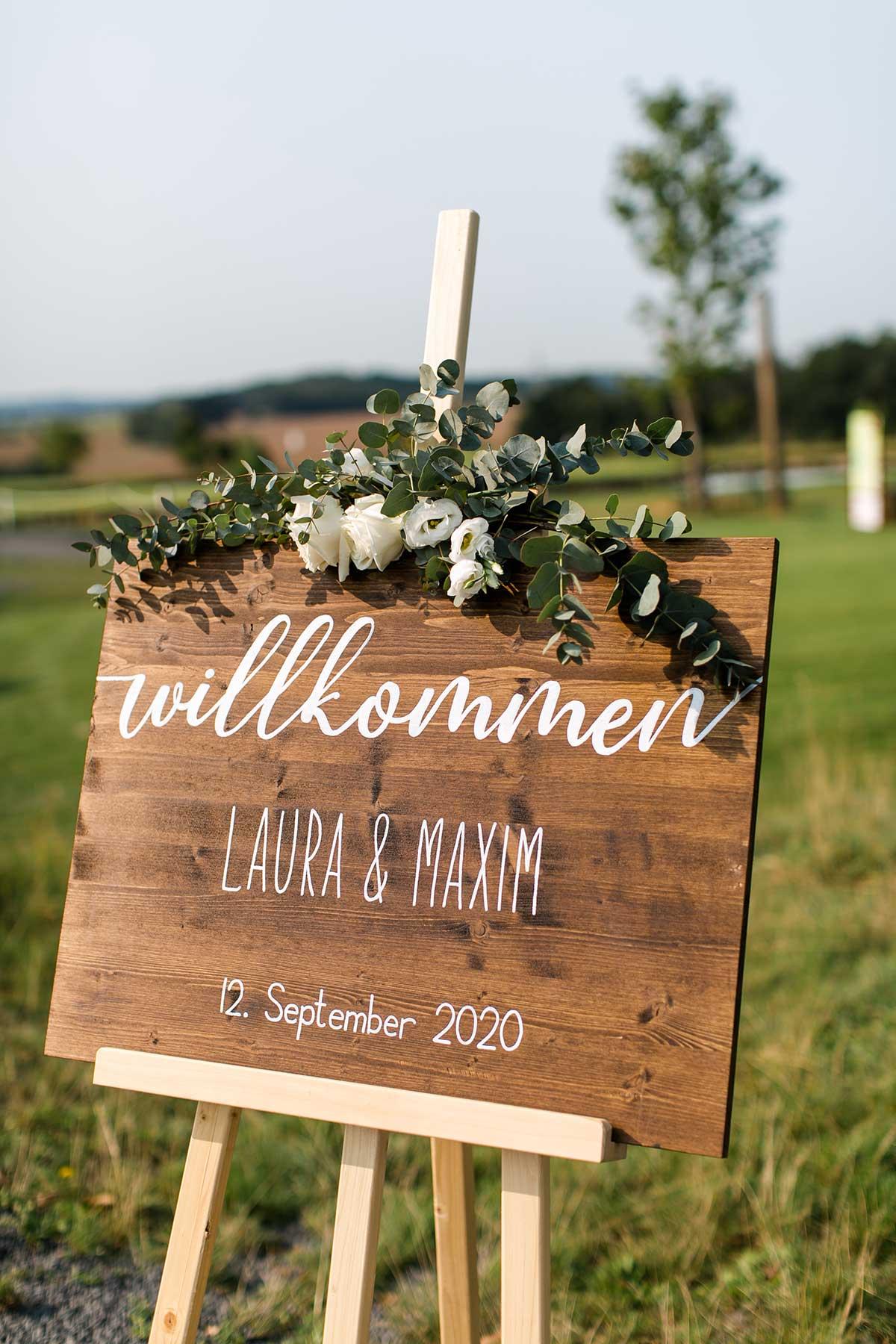Willkommensschild aus Holz bei der Hochzeit