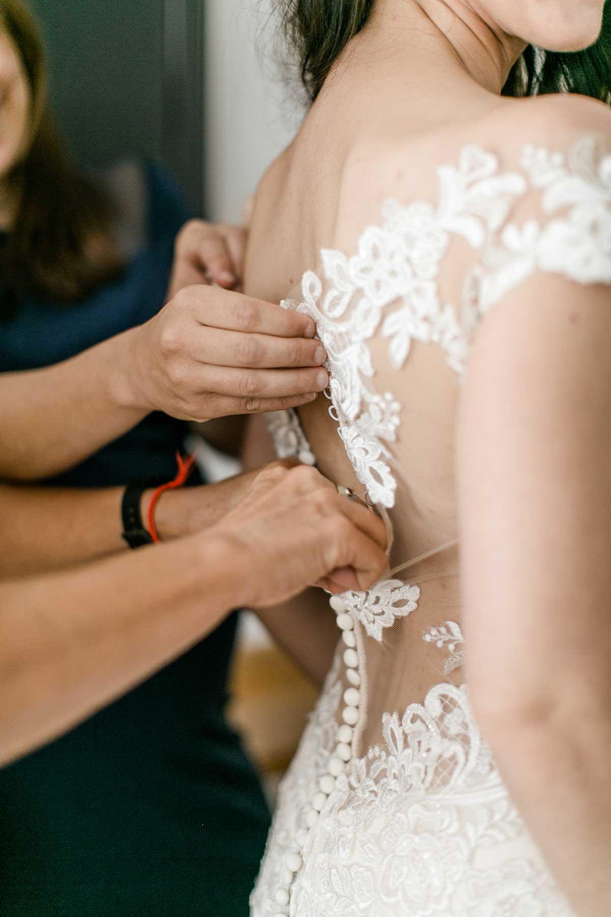 Braut bekommt das Brautkleid zugeknöpft
