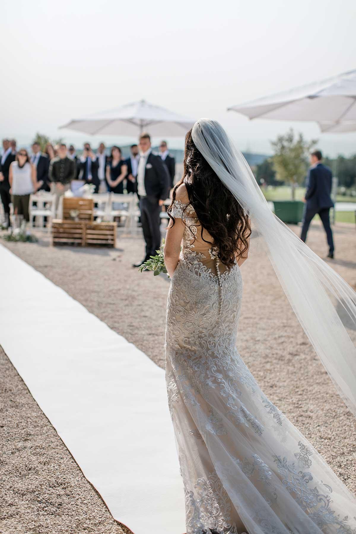 Braut auf dem Weg zum Traubogen