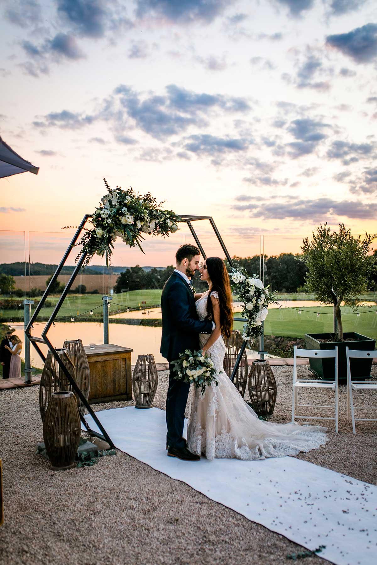 Braut und Bräutigam beim Fotoshooting im Sonnenuntergang