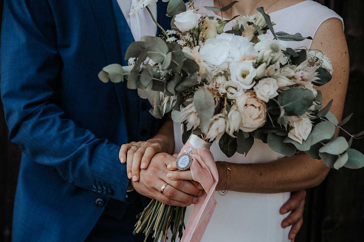 Brautpaar hält Brautstrauß mit Memorial