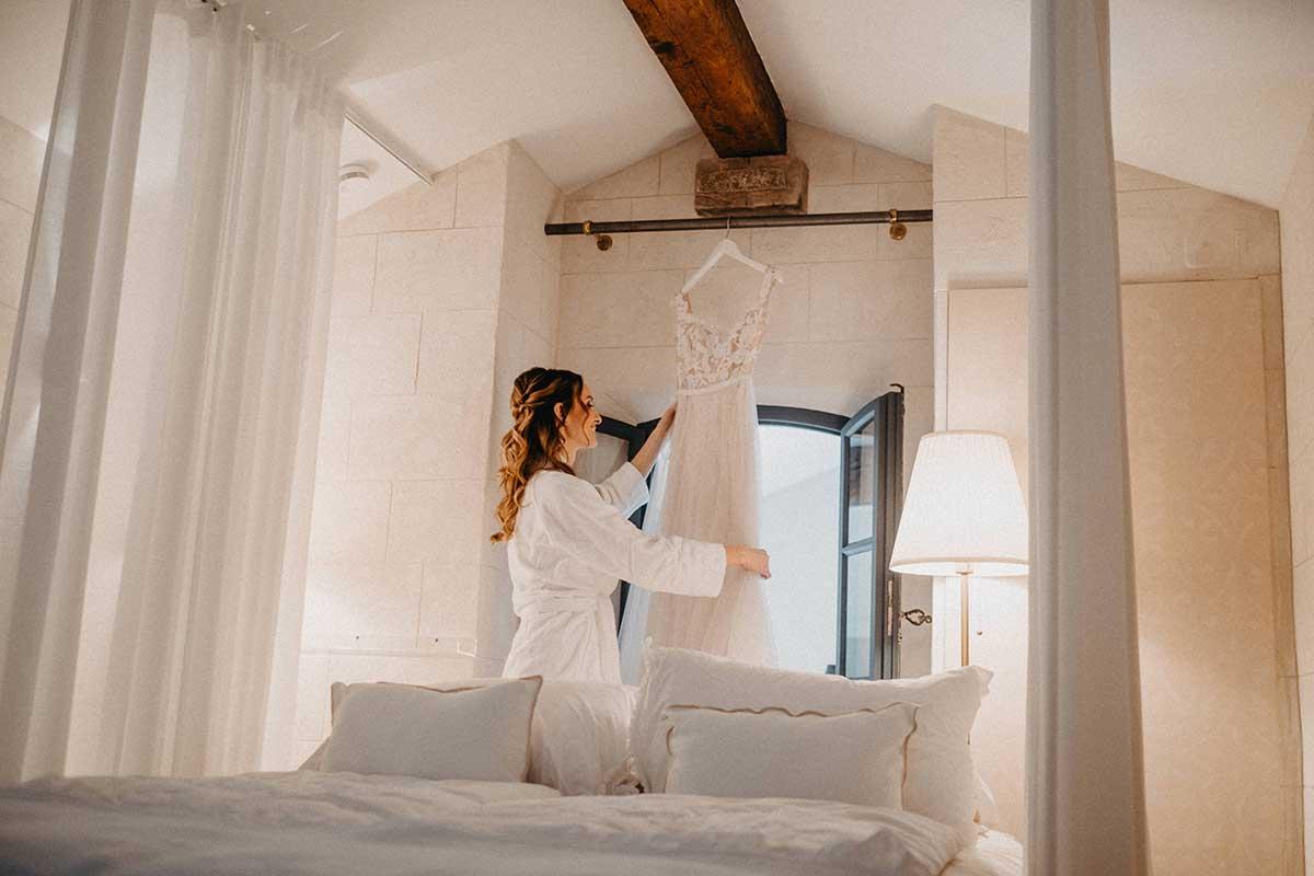 Braut schaut sich ihr Brautkleid beim Getting Ready an