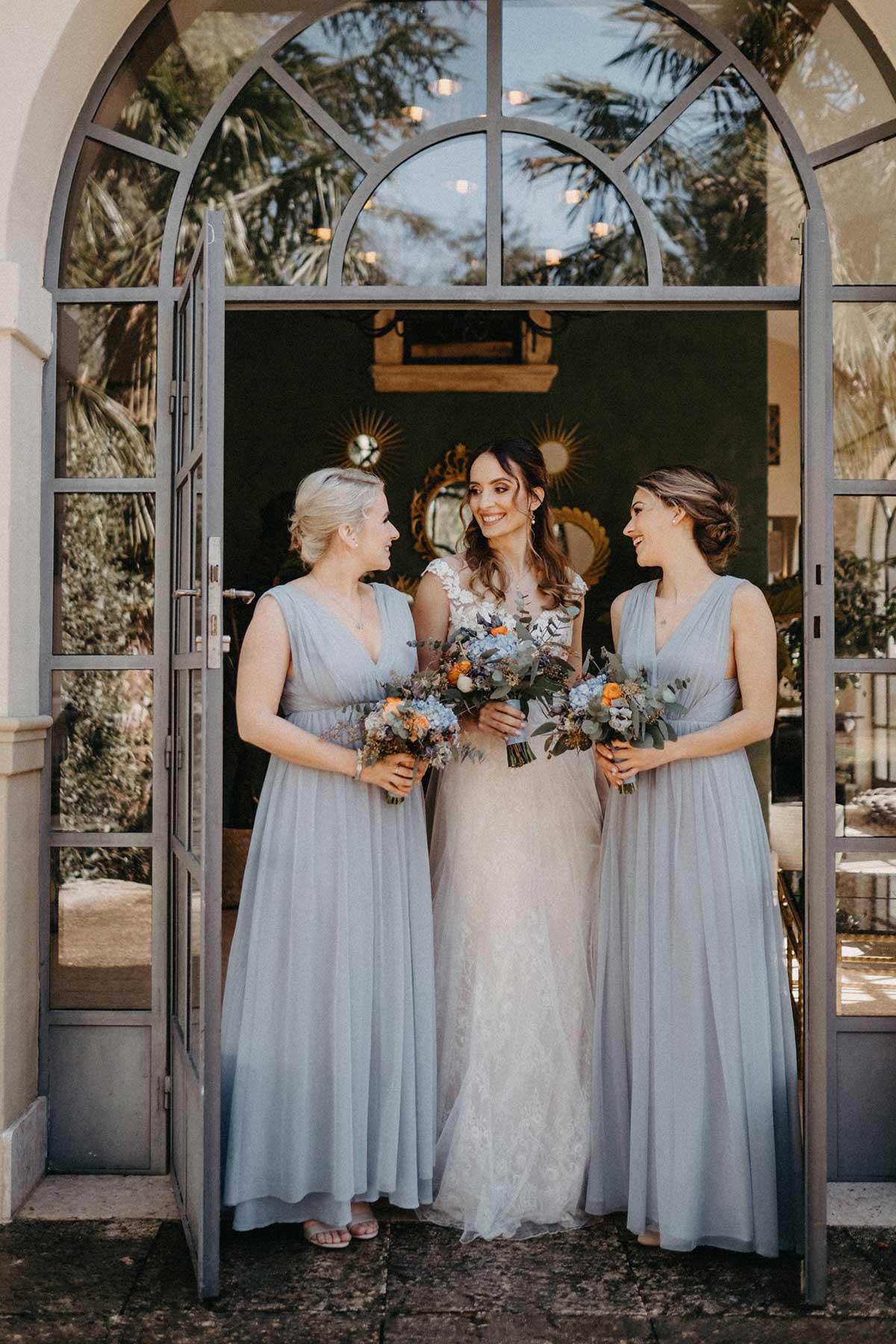 Braut mit ihrem Brautstrauß und ihren Brautjungfern in taubenblauen Kleidern