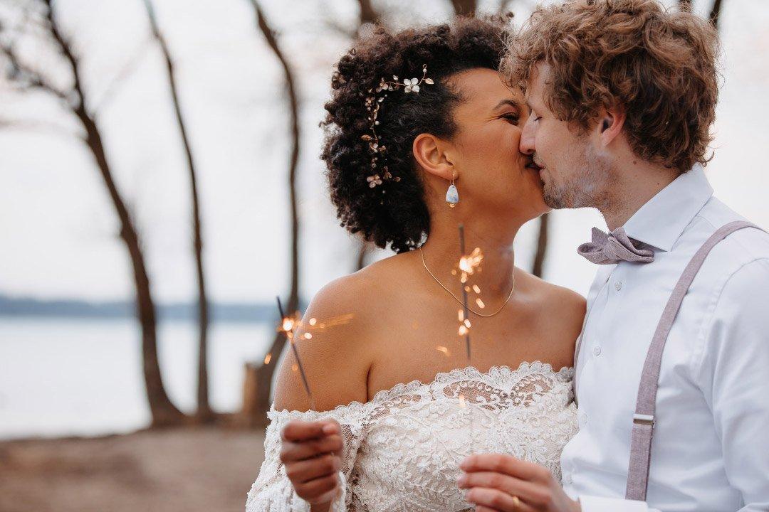 Braut und Bräutigam halten brennende Wunderkerze