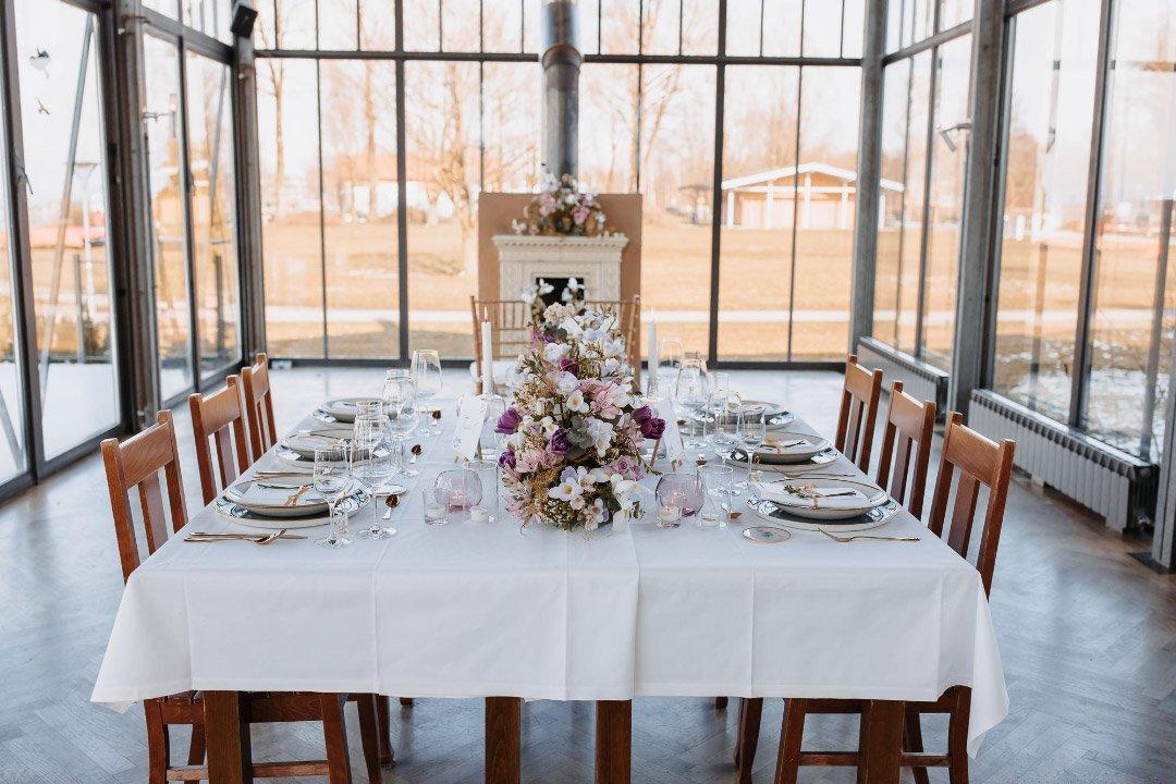 Gedeckter Hochzeitstisch mit oppulenten Blütengesteck