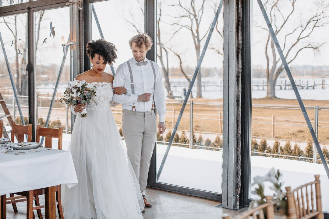 Brautpaar auf dem Weg zum gedeckten Tisch