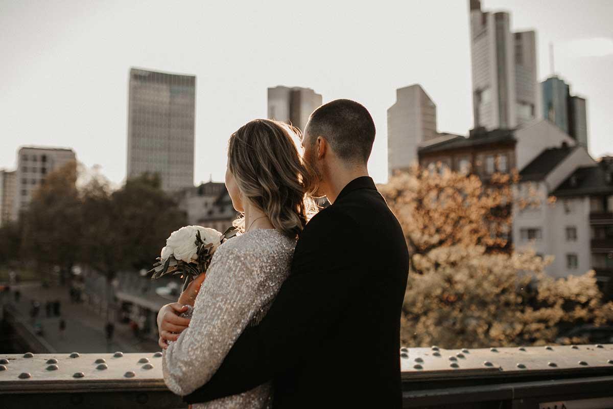 Braut und Bräutigam schauen über Brücke hinweg