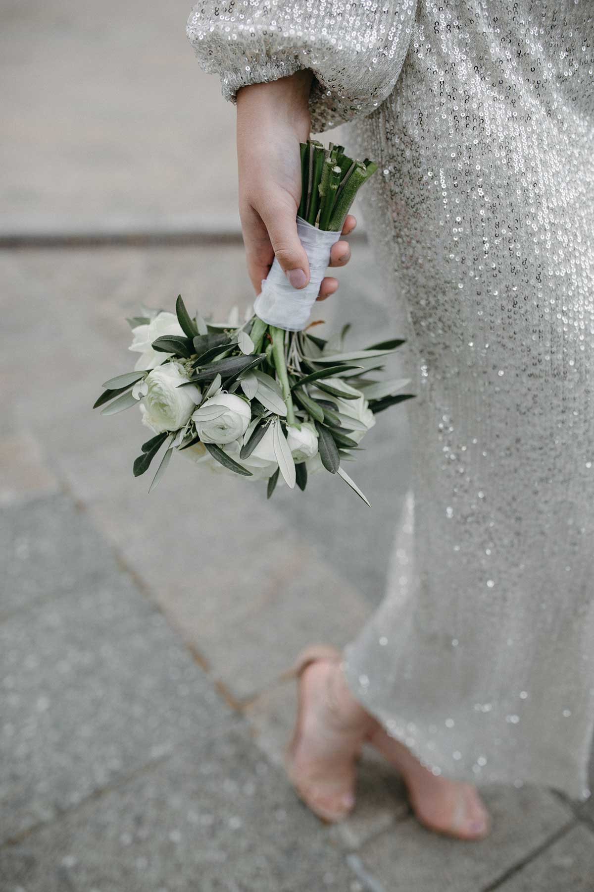 Braut hält Brautstrauß mit weißen Blumen