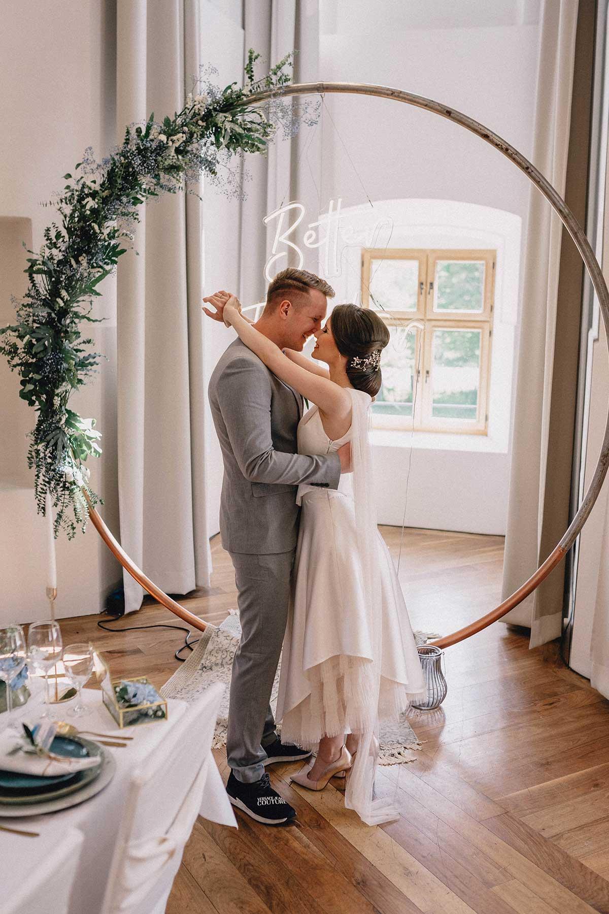 Braut und Bräutigam vor dem Traubogen mit Neon Letters