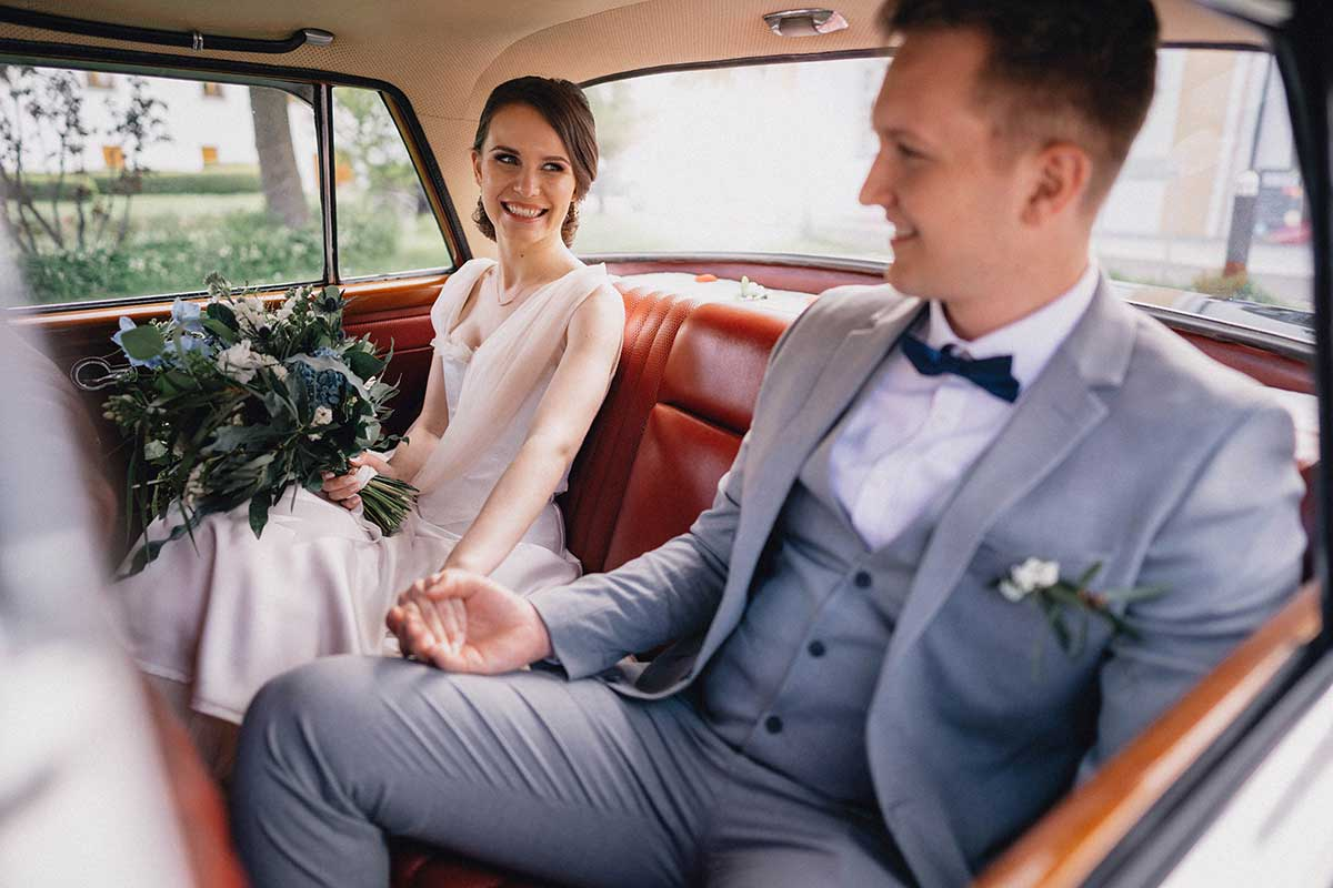 Brautpaar sitzt im Auto